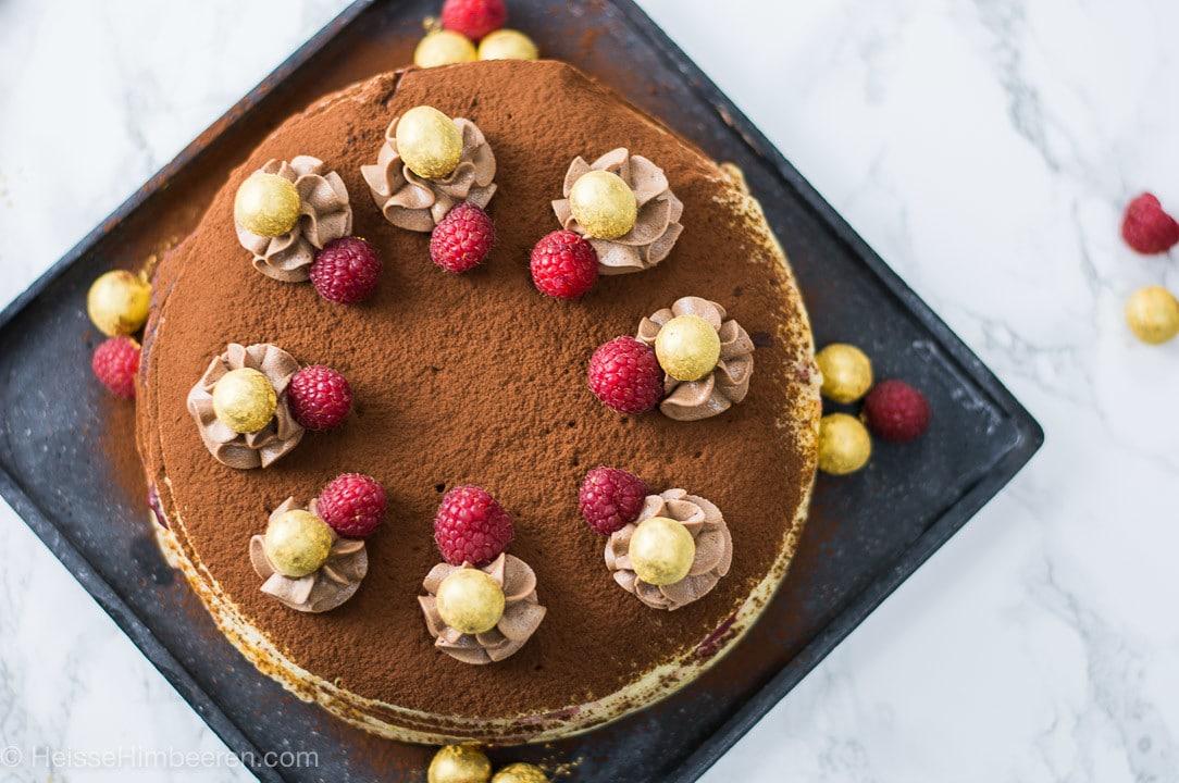 Eine Crepe Torte von oben. Sie ist dekoriert mit Kakaopulver, Creme, goldenen Kugeln und Himbeeren