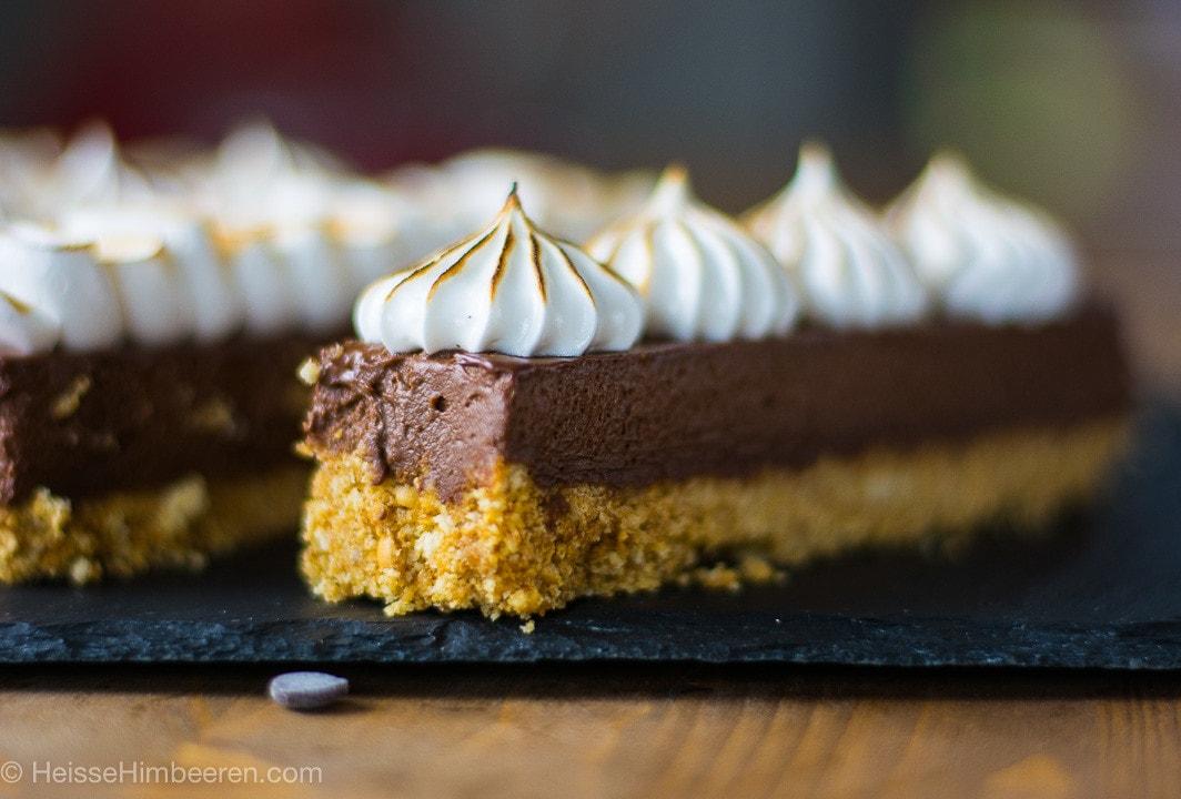 Ein S'Mores Kuchen mit Baiserhaube auf einer schwarzen Schiefernplatte