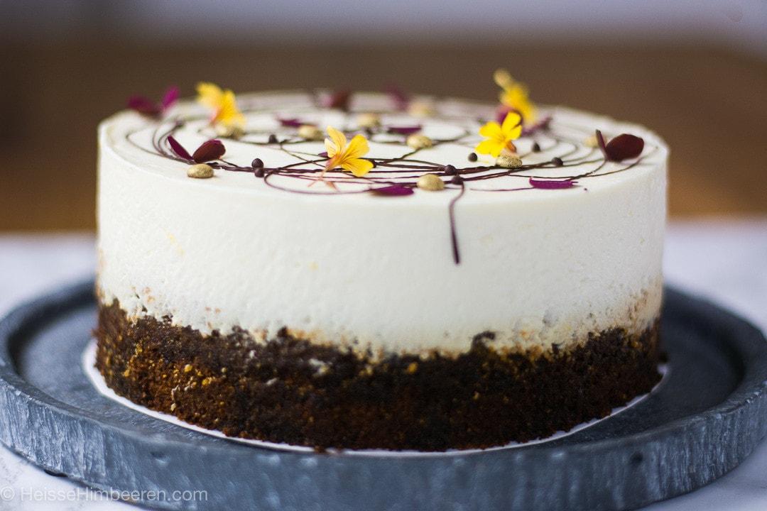 Der Butternut Kürbis Kuchen von der Seite. Man sieht einen Schokoladenboden und eine weiße Creme darüber