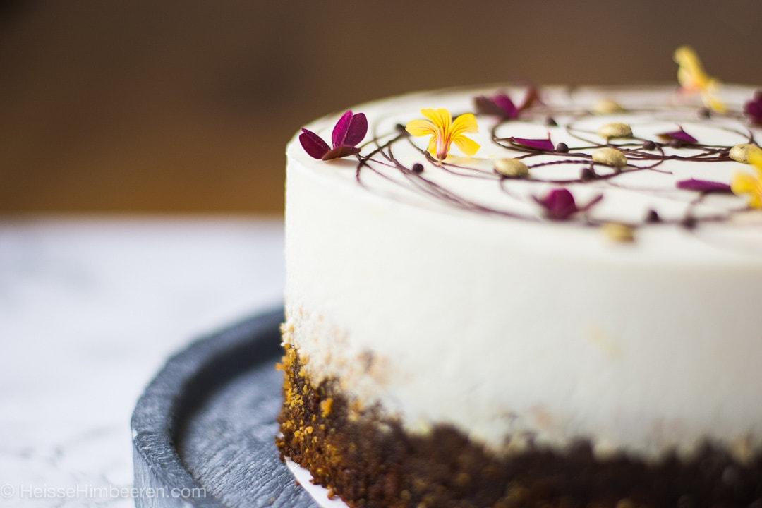 Der Kuchen von der Seite. Im Fokus stehen die Blüten als Dekoration auf dem Kuchen