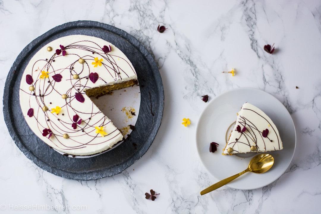 Der Butternut Kürbis Kuchen von oben. Die Dekoration aus Schokolade und Blüten ist sehr fein und edel