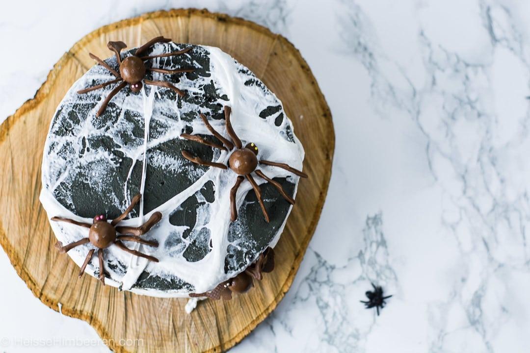 Halloween Kuchen von der oben. Man sieht drei Schokoladen Spinnen und einen Spinnennetz über dem Kuchen