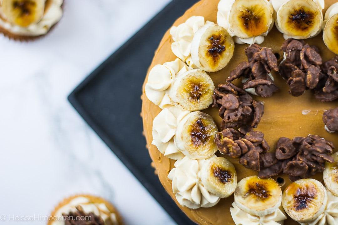 Die Bananen Torte on oben. Daneben stehen zwei Bananen Cupcakes