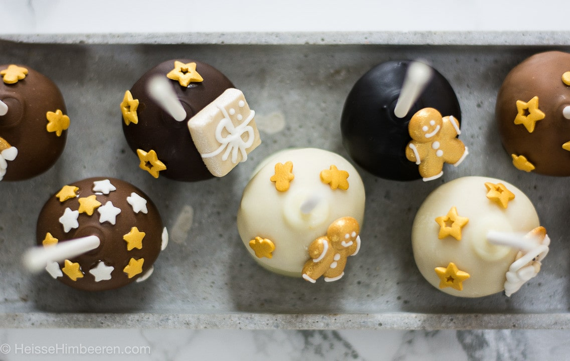 Meherere Weihnachts Cake Pops von oben. Sie sind in weißer, heller und dunkler Schokolade