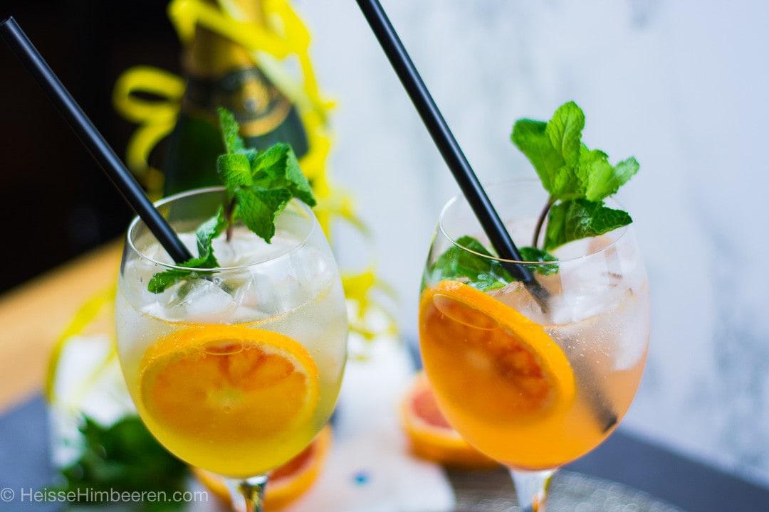 Aperitif mit Gin und Prosecco in einem Weinglas mit schwarzen Strohhalm