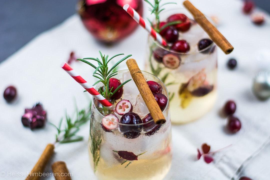 Zwei weihnachtliche Cocktails mit Rosmarin Zweigen, Cranberries und Zimtstangen