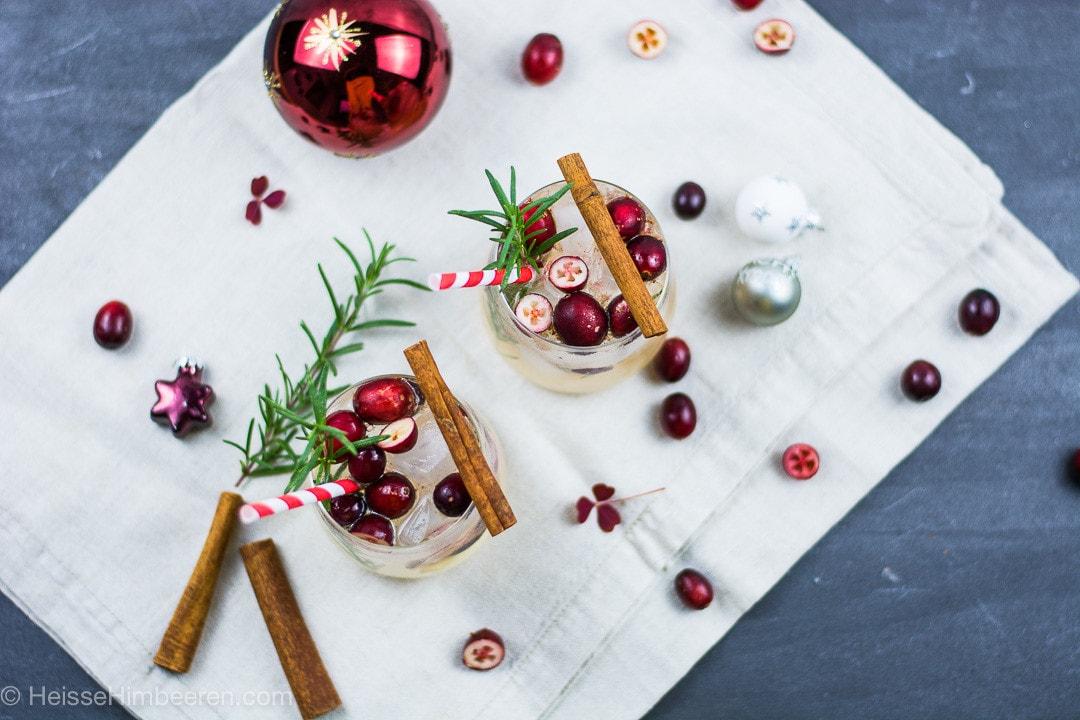 Zwei weihnachtliche Cocktails von oben auf einem weihnachtlich gedeckten Tisch