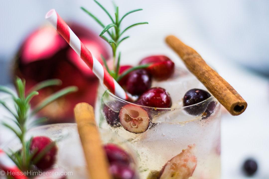 Eine Nahaufname des weihnachtlichen Moscow mules mit Cranberry, Zimtstange und Rosmarin