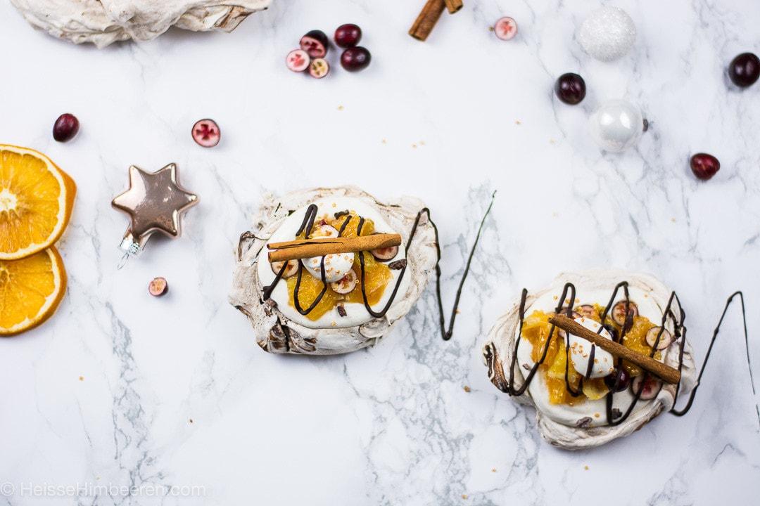 Zimtstangen und Schokolade liegen auf den weihnachtlichen Pavlovas