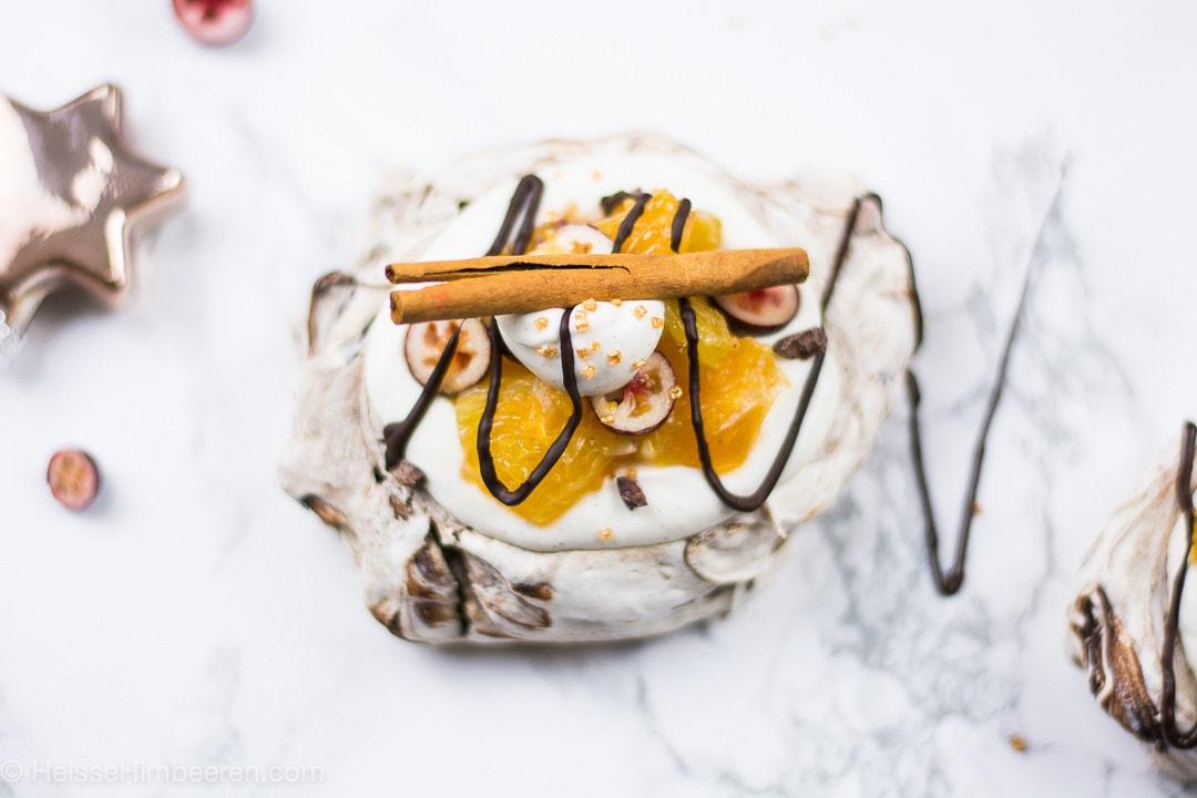 Man sieht eine Zimtstange, Creme und Orangen auf einer Pavlova
