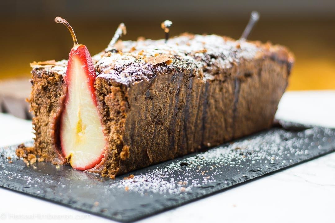 Ein angeschnittener Schoko Birnen Kuchen in Kastenform. Er steht auf einer Schieferplatte