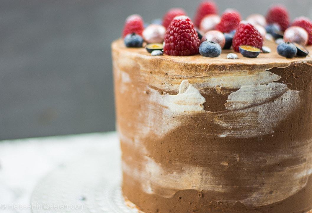 Die Schokotorte ist mit einer Schokoladenschicht umhüllt. Auf der Torte liegen viele verschiedene Beeren
