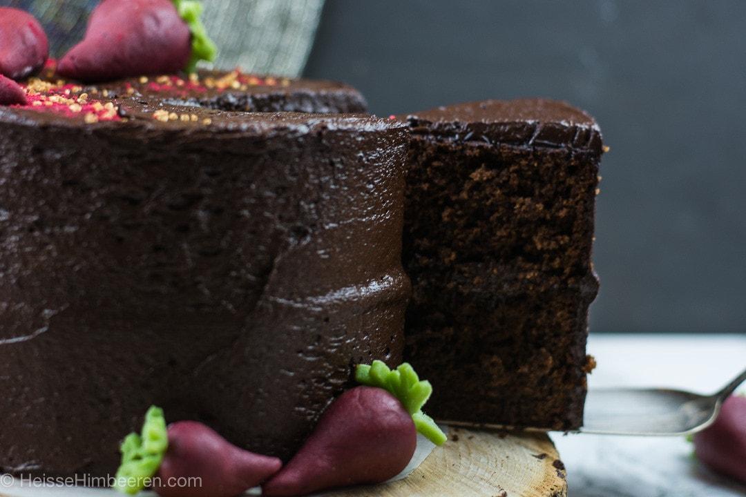 Ein Stück saftiger Schokoladenkuchen mit Roter Bete wird mit einer Kuchenschaufel aus dem Kuchen genommen