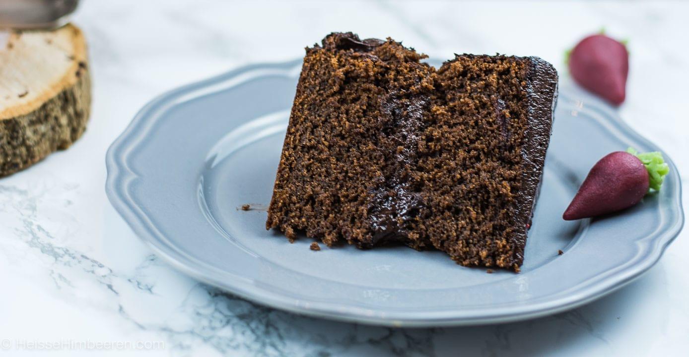 Ein Stück des Schokoladenkuchens. An der Seite liegen Rote Beete aus Marzipan als Deko