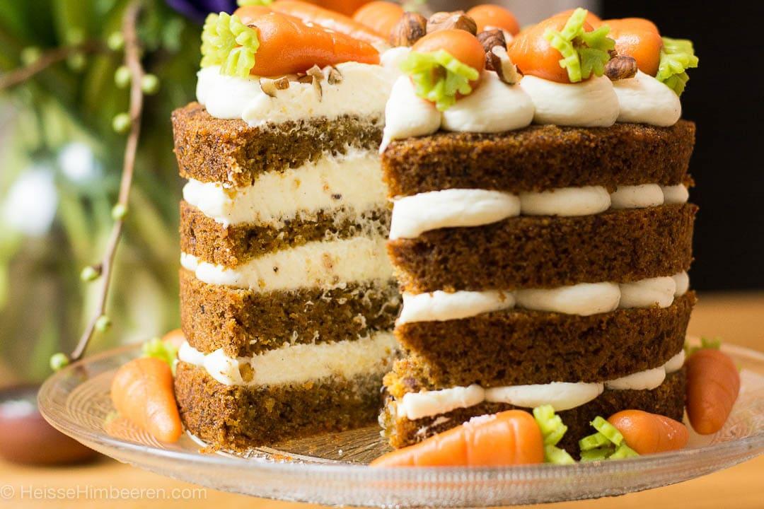 Ein angeschnittener Karottenkuchen mit Marzipan Karotten auf und neben dem Kuchen
