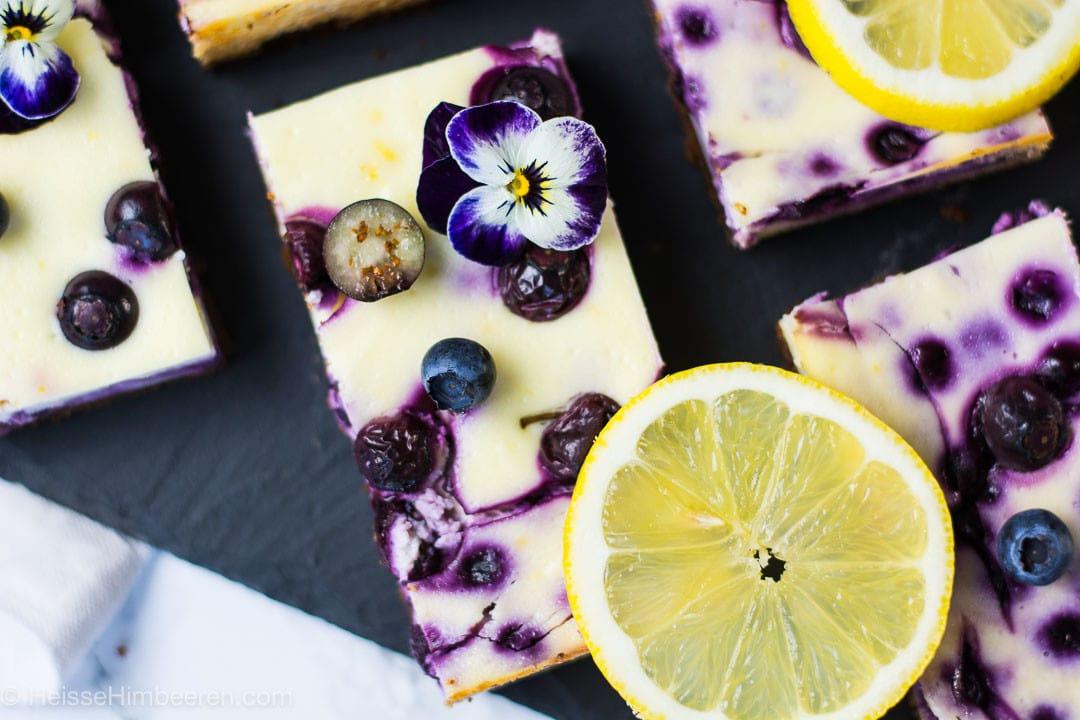 Blaubeer Käsekuchen Stücke, dekoriert mit Zitronen und Blaubeeren