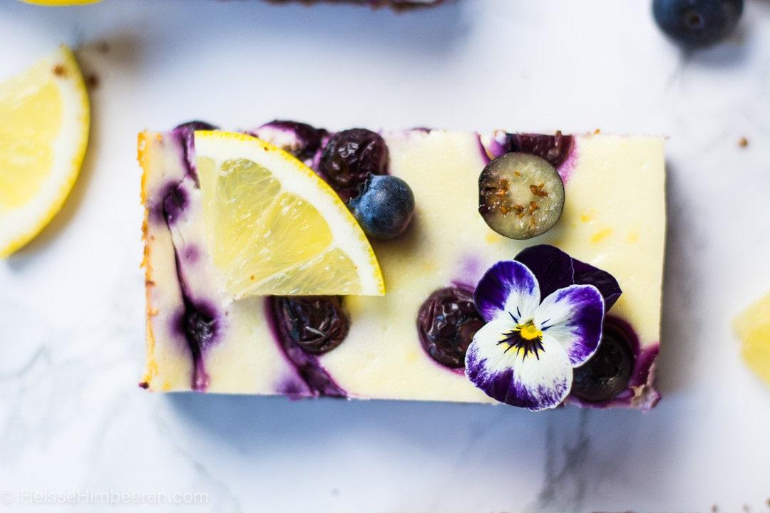 Ein Stück Käsekuchen mit Blaubeeren und einem viertel Zitrone