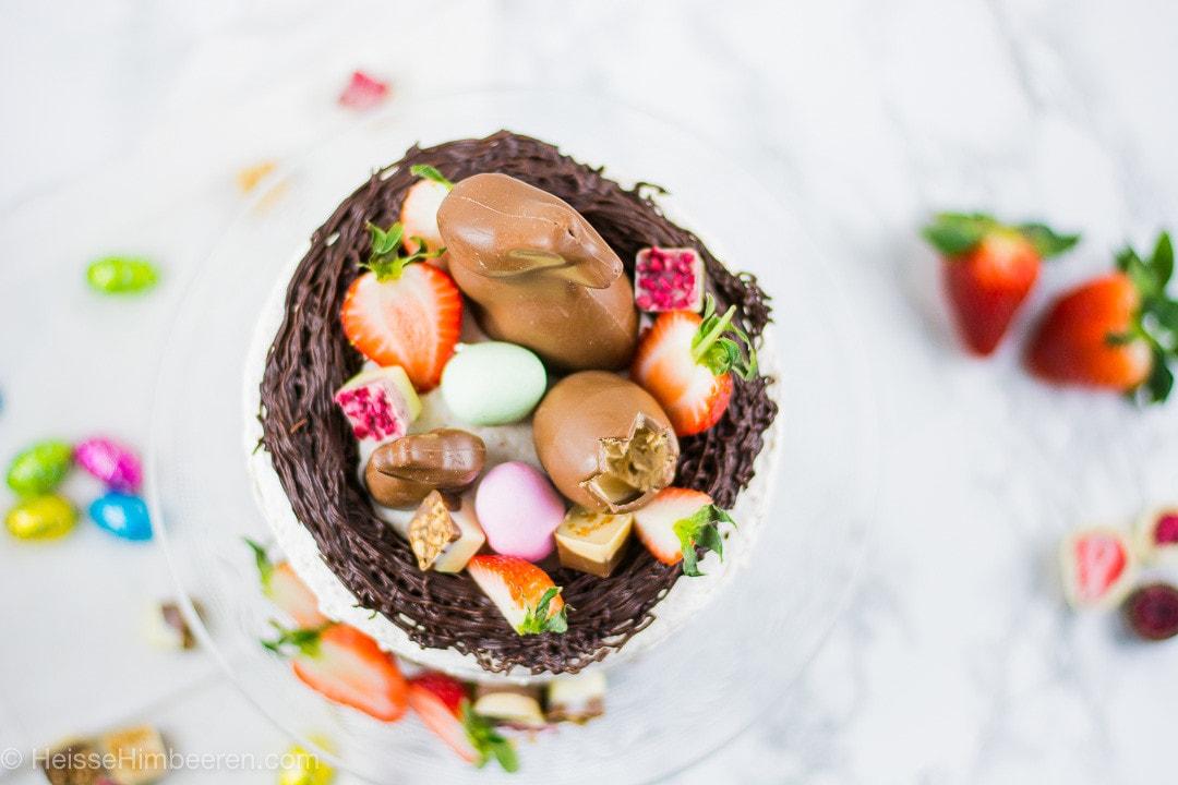 Man erkennt einen Osterhasen, Pralinen und Erdbeerhälften im essbares Osternest auf der Ostertorte