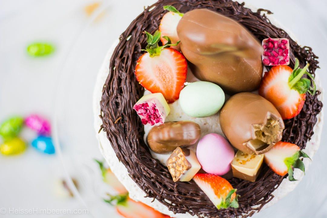 Ein essbares Osternest mit Pralinen, Erdbeerhälften und Schokoladenhasen