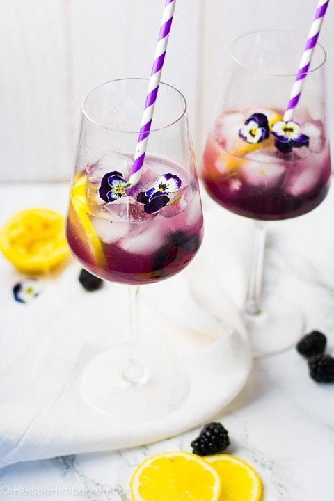 Zwei Gläser mit einem Aperitif gefüllt. Als Dekoration haben die Gläser blaue Blüten