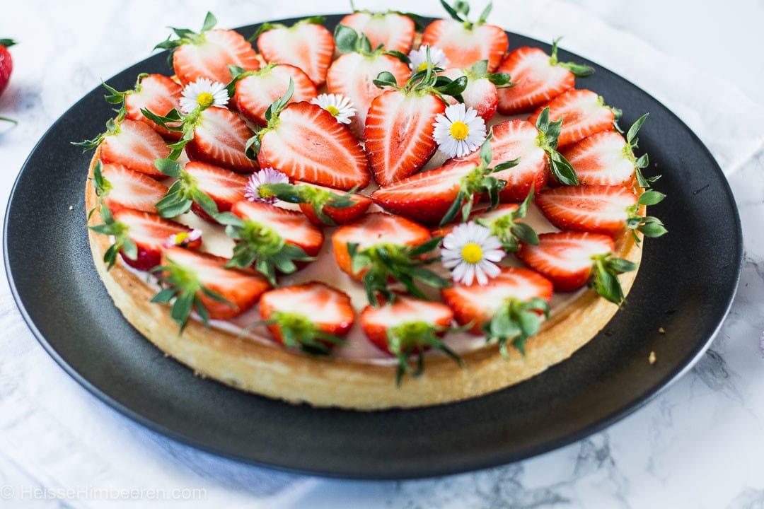 Ein Erdbeerkuchen auf einem schwarzen Teller. Die Erdbeeren sind alle halbiert