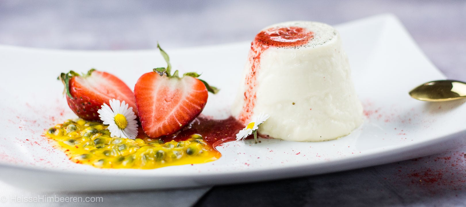 Ein Teller mit Panna Cotta, roter Erdbeersauce, Maracujakernen und zwei Erdbeerhälften