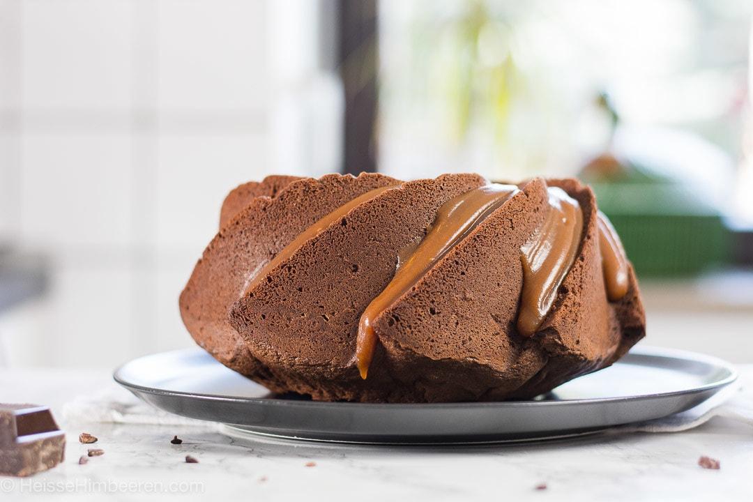 Ein Schokokuchen mit Karamell auf einem schwarzen teller. Davor liegt ein Stück Schokolade