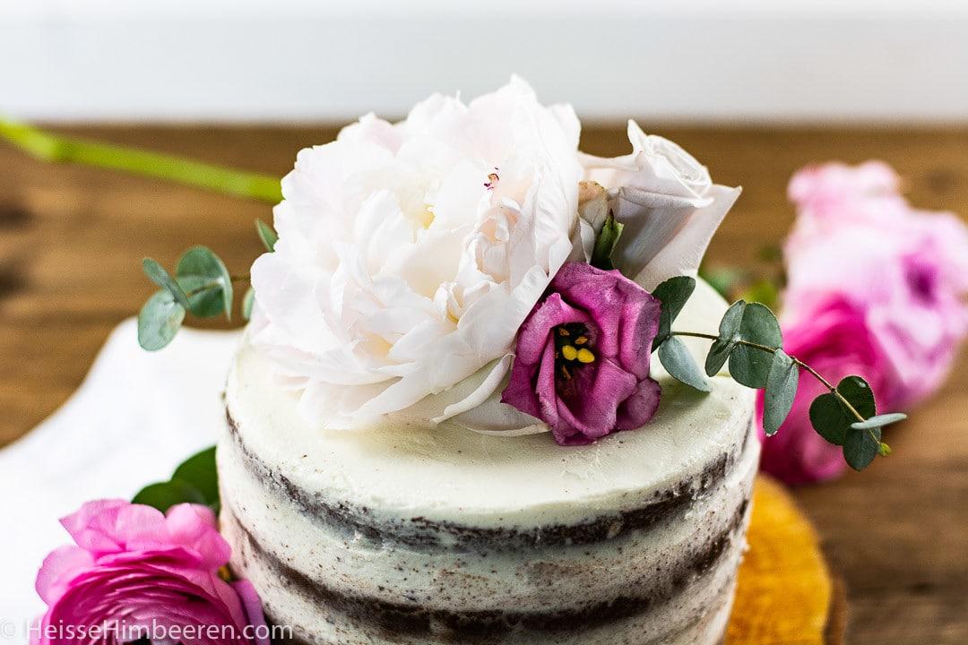 Man erkennt weiße und bunte Blumen auf einer Geburtstagstorte