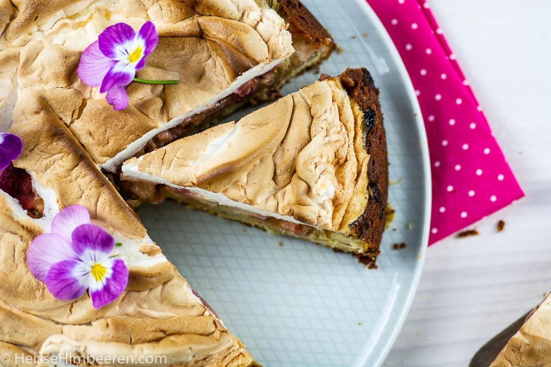 Ein angeschnittener Rhabarberkuchen. Ein Stück Kuchen ist an der Seite