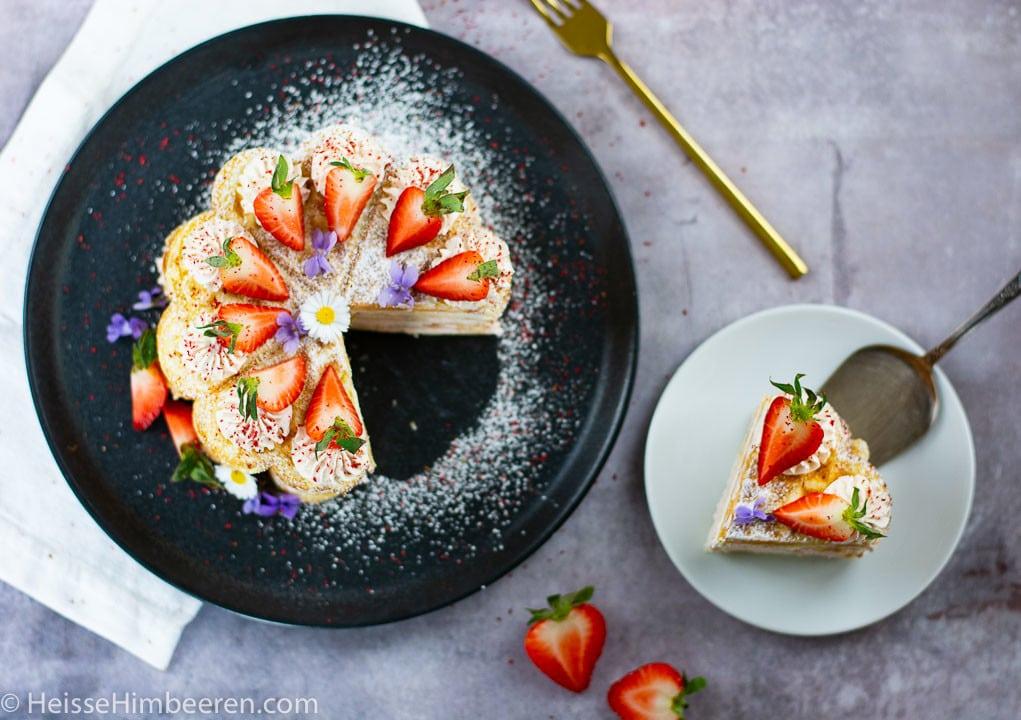 Eine Waffeltorte mit Erdbeeren auf einem schwarzen Teller