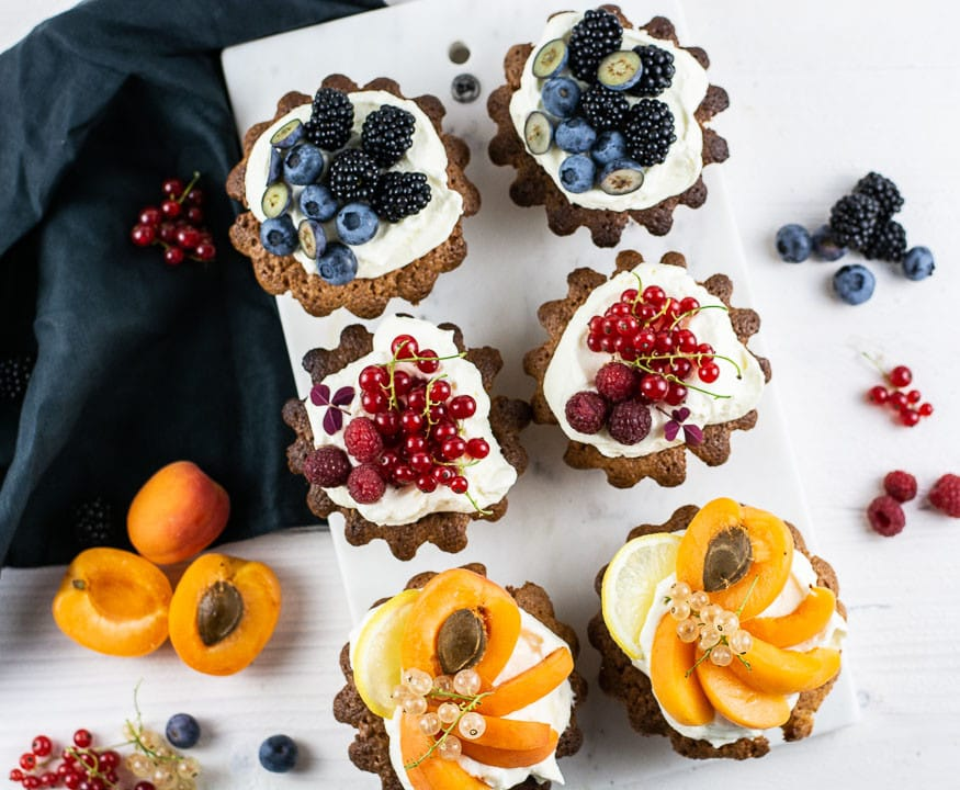 Sechs Mandelkuchen mit Obst auf einer Mamorplatte