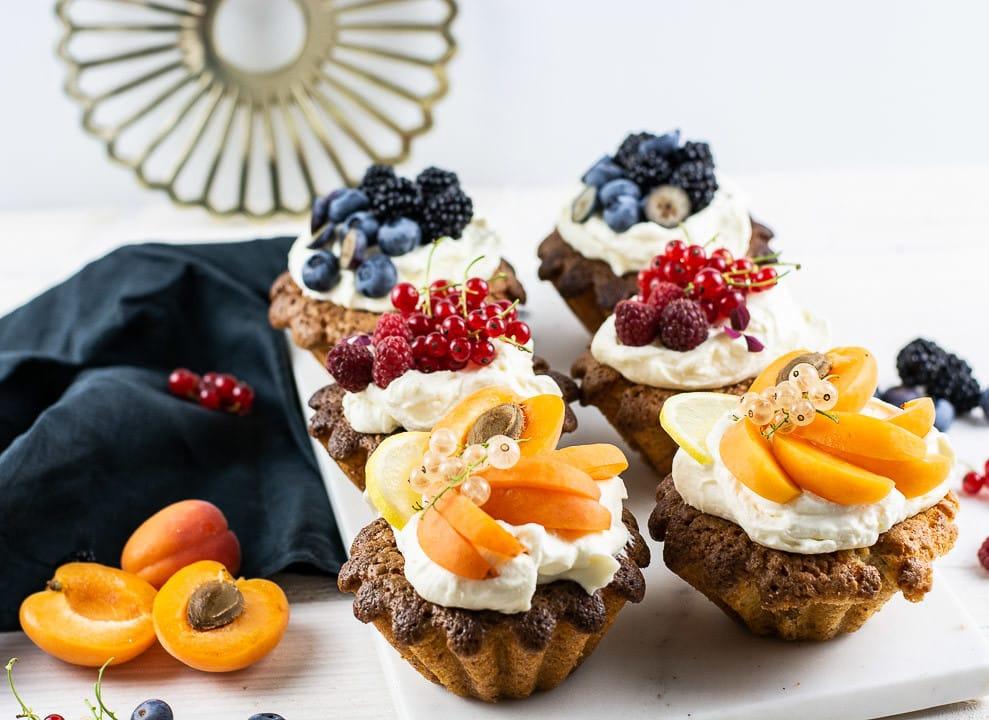 Sechs Mandelkuchen mit Obst. Daneben liegen Pfirsiche als Dekoration