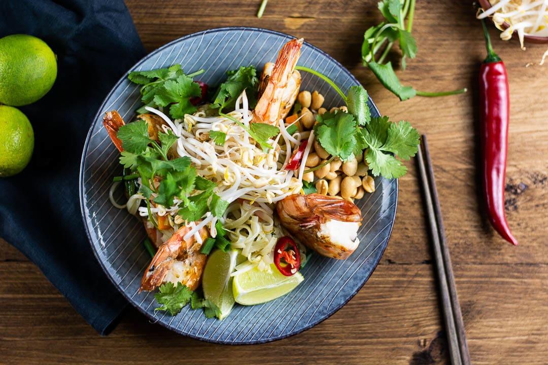 Ein Pad Thai mit Garnelen auf einem blauen Teller. Daneben liegen zwei Stäbchen und eine Chili