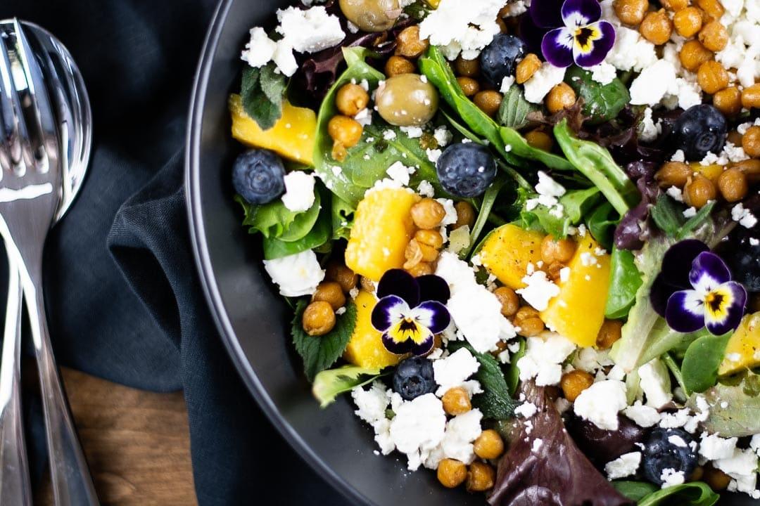 Ein Salat in einer dunklen Schüssel mit Besteck daneben