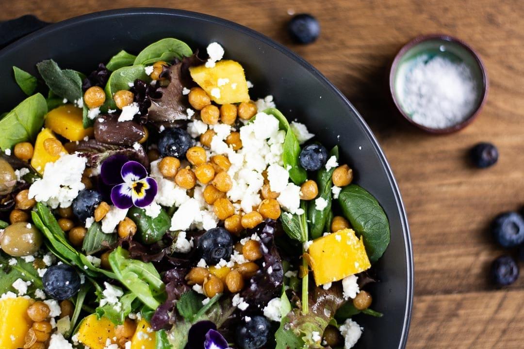 Ein Schüssel Salat mit Blaubeeren an der Seite als Dekoration