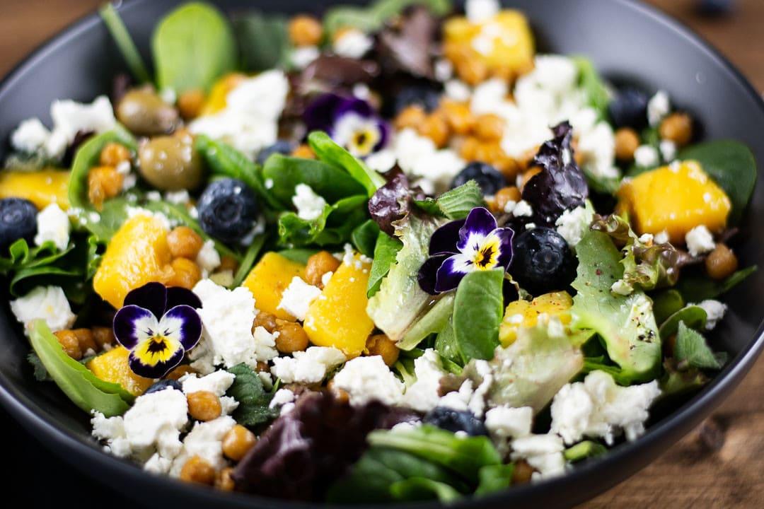 Der Orientalischer Salat in der Nahaufnahme. Man sieht Blaubeeren, Mango und Kichererbsen