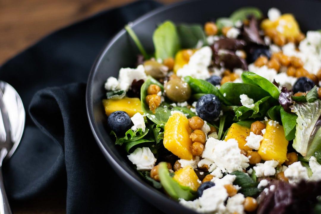 Man sieht Mangostücke, Kichererbsen, Blaubeeren, Feta und Salat