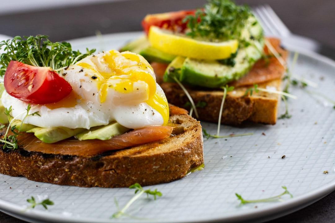 Ein pochiertes Ei mit Avocado, Lach und Tomate auf einem Stück Brot