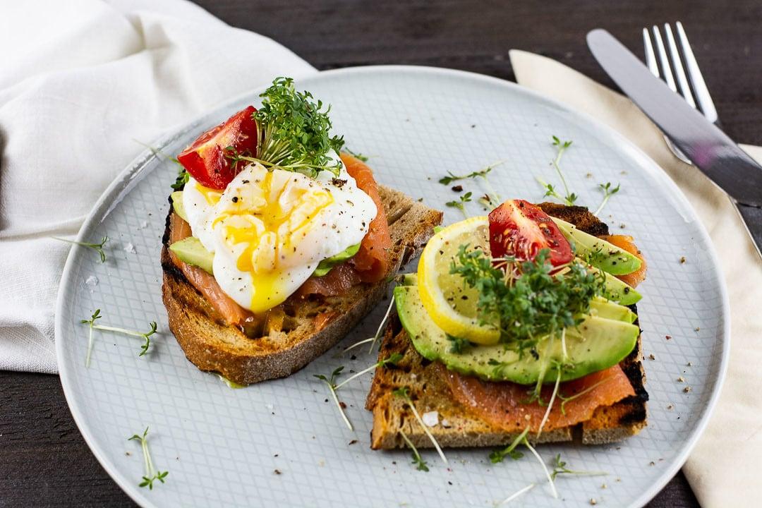 Zwei Avocado Toast mit pochiertes Ei auf einem Teller mit Besteck daneben