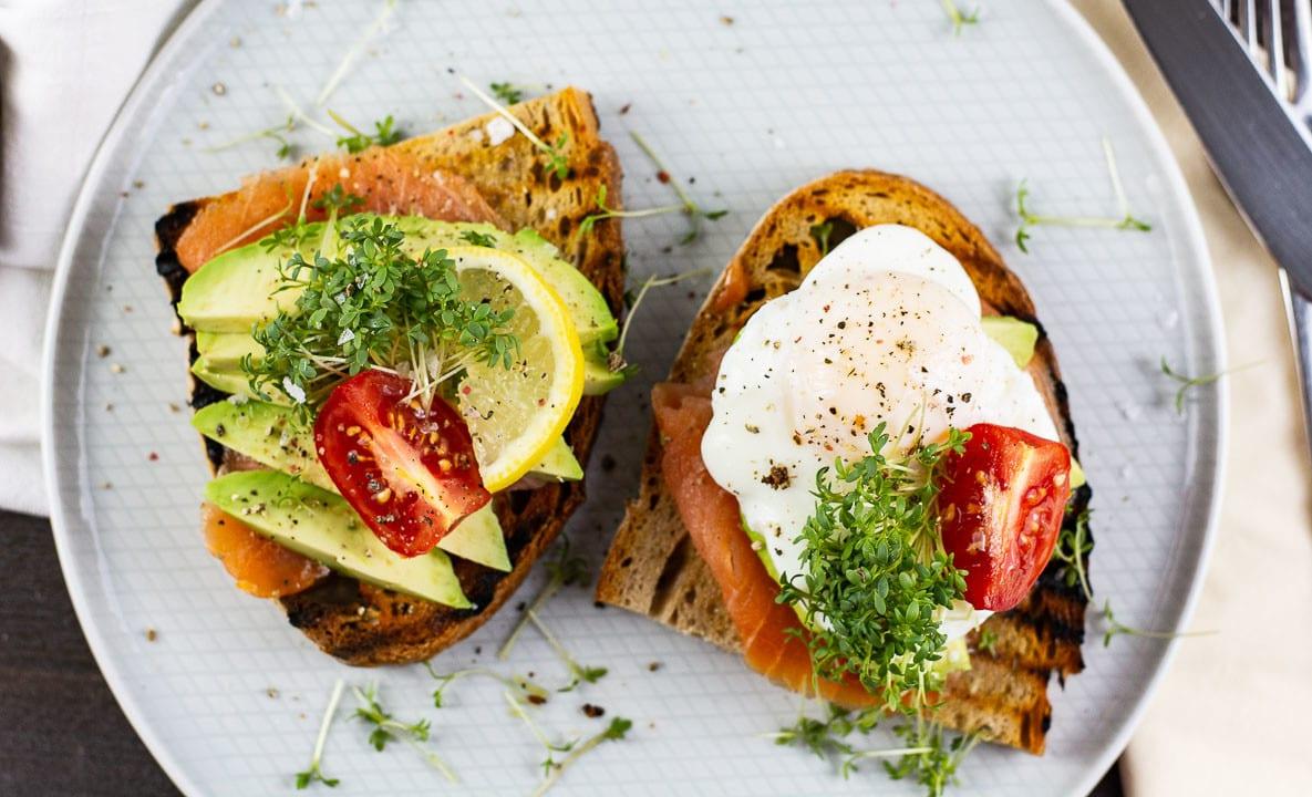 Zwei Avocado Toasts von oben. Man sieht ein pochiertes Ei, Avocado, Lachs und Tomaten auf den Toast.