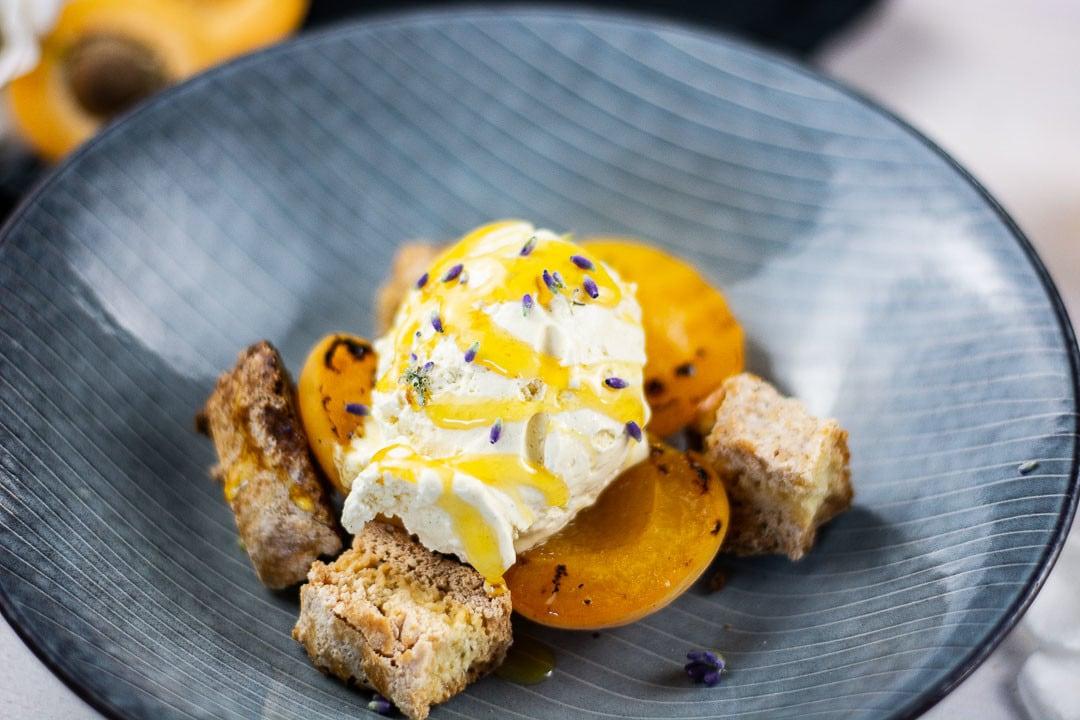 Nahaufnahme einer Kugel Eis mit Honig, sowie gegrillten Aprikosen und Cantuccini