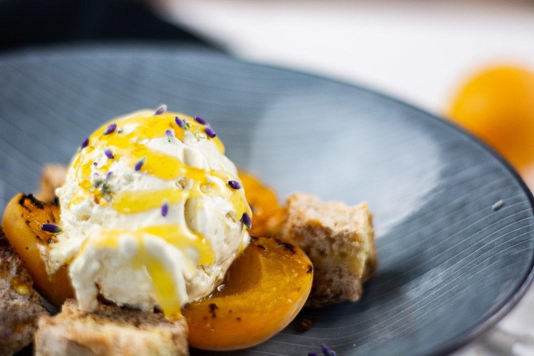 Kugel Vanilleeis mit Honig beträufelt auf einem Teller