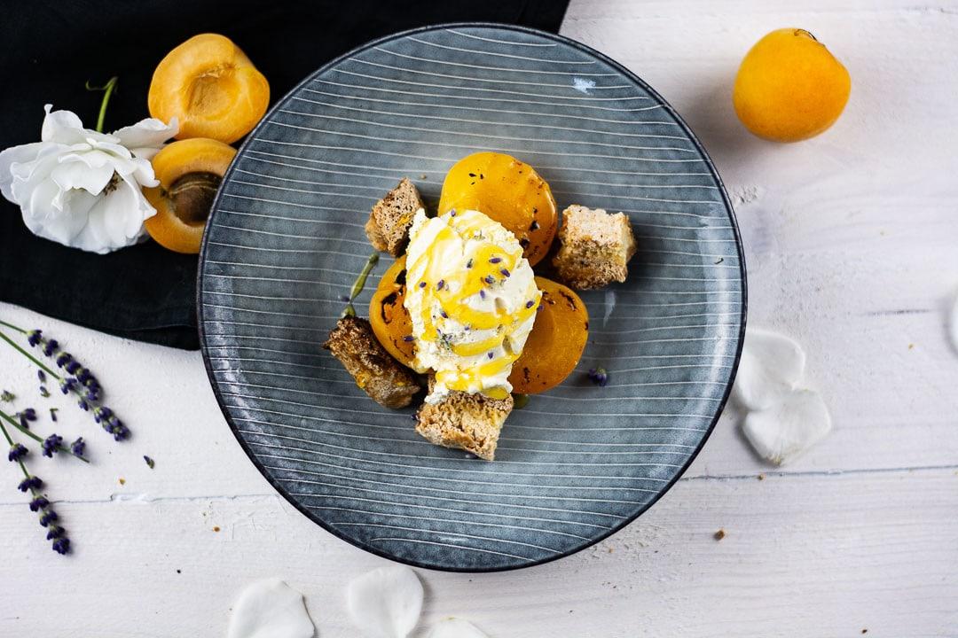 Ein Dessert vom Grill. Auf einem Teller liegen Cantuccini mit gegrillten Aprikosen und einer Kugel Vanilleeis