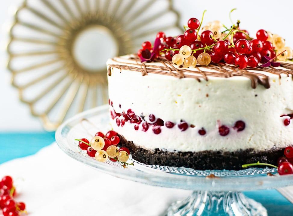 Ein Käsekuchen ohne backen auf einer Kuchenplatte. Der Kuchen ist bedeckt mit Johannisbeeren