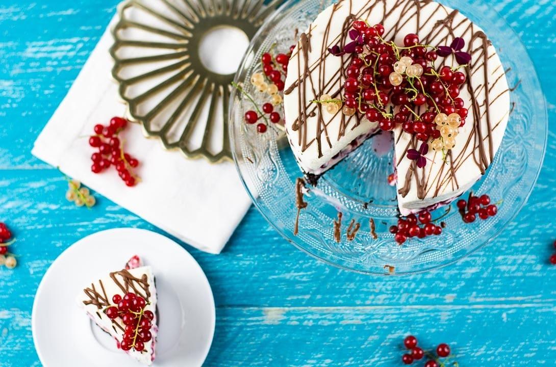 Ein angeschnittener Käsekuchen. Neben dem Kuchen steht ein Teller mit einem Stück des Käsekuchens