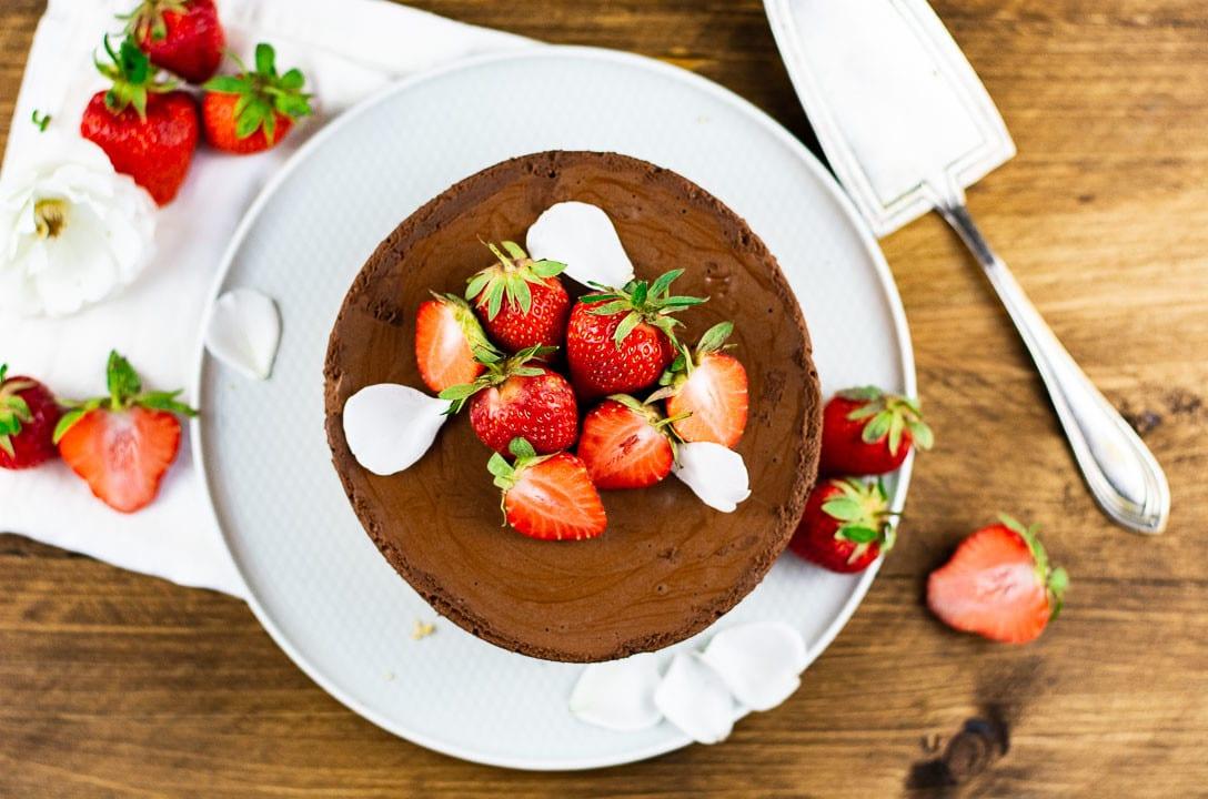 Die Erdbeertorte mit Schokoladenmousse von oben. Auf der Torte liegen Erdbeeren und ein paar weiße Blütenblätter