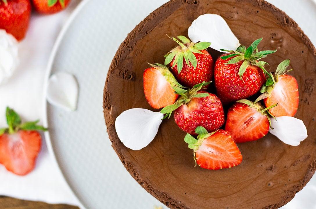 Die Erdbeertorte mit Keksboden von oben. Dekoriert mit vielen Erdbeeren und weißen Blütenblättern