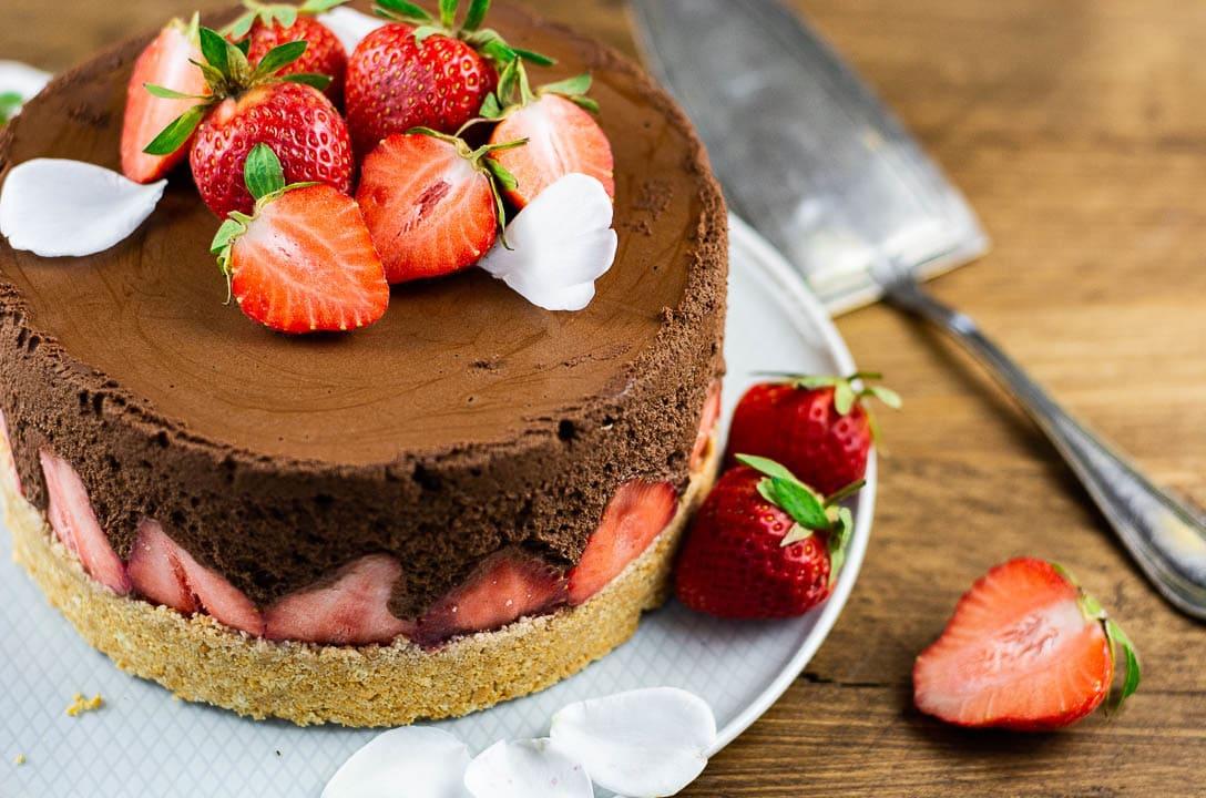 Eine Erdbeertorte, die nicht gebacken werden muss auf einem Teller. Daneben liegt ein Tortenheber