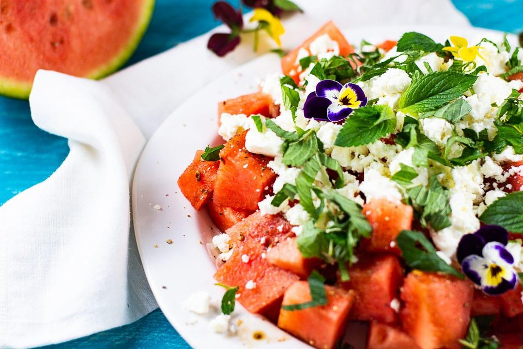 Ein Wassermelonensalat mit Feta und Minze in der Nahaufnahme. Der Salat liegt auf einem weißen Teller