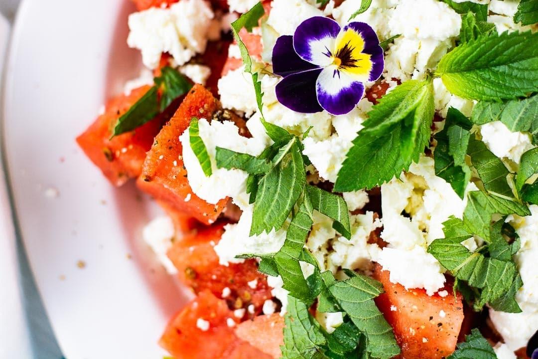 Eine Nahaufnahme des Salates. Man sieht Minzblätter, Wassermelone und Feta